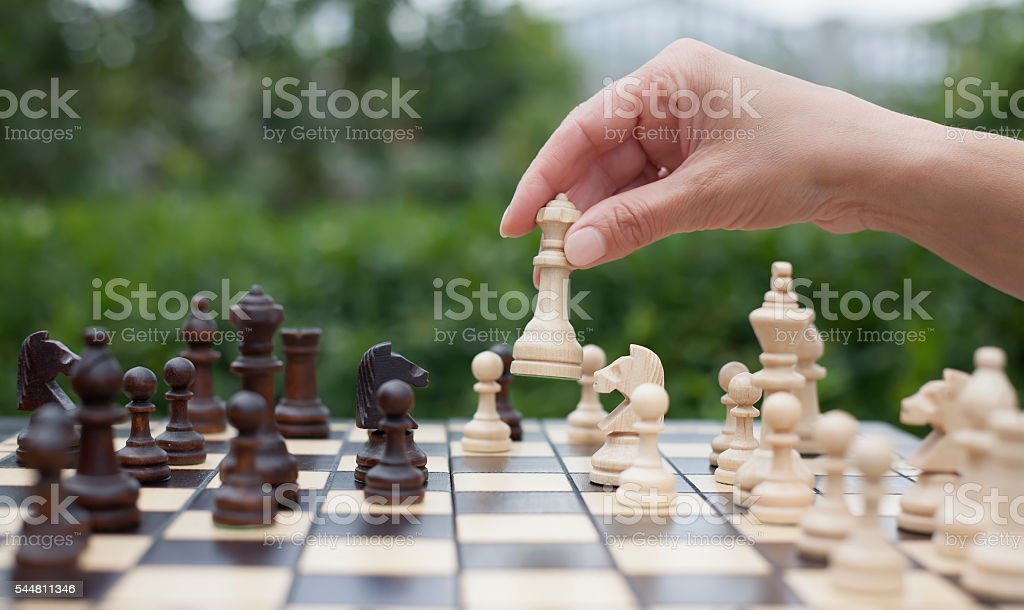 woman's hand moves a piece of queen on chessboard stock photo