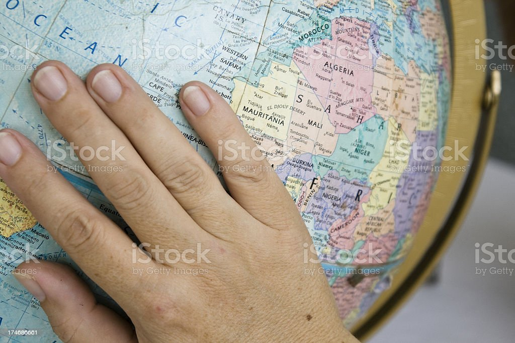 Woman's Hand on a Globe royalty-free stock photo