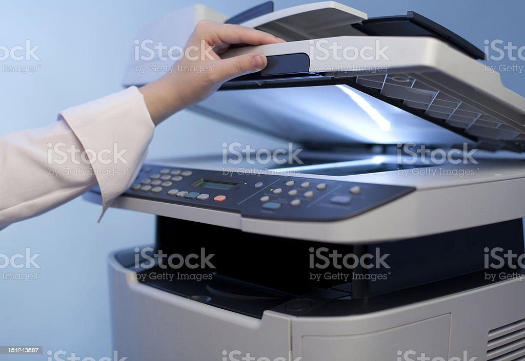 A woman's hand on the scanner part of a printer stock photo