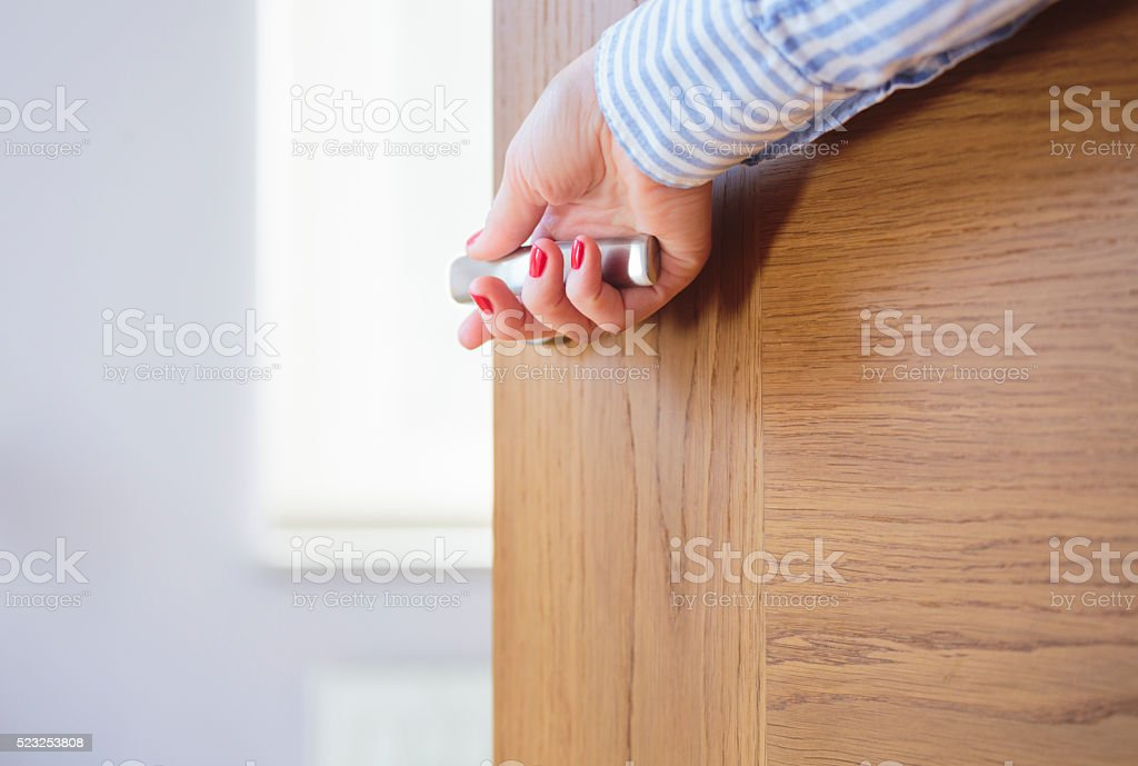 Woman's hand opening a door. stock photo