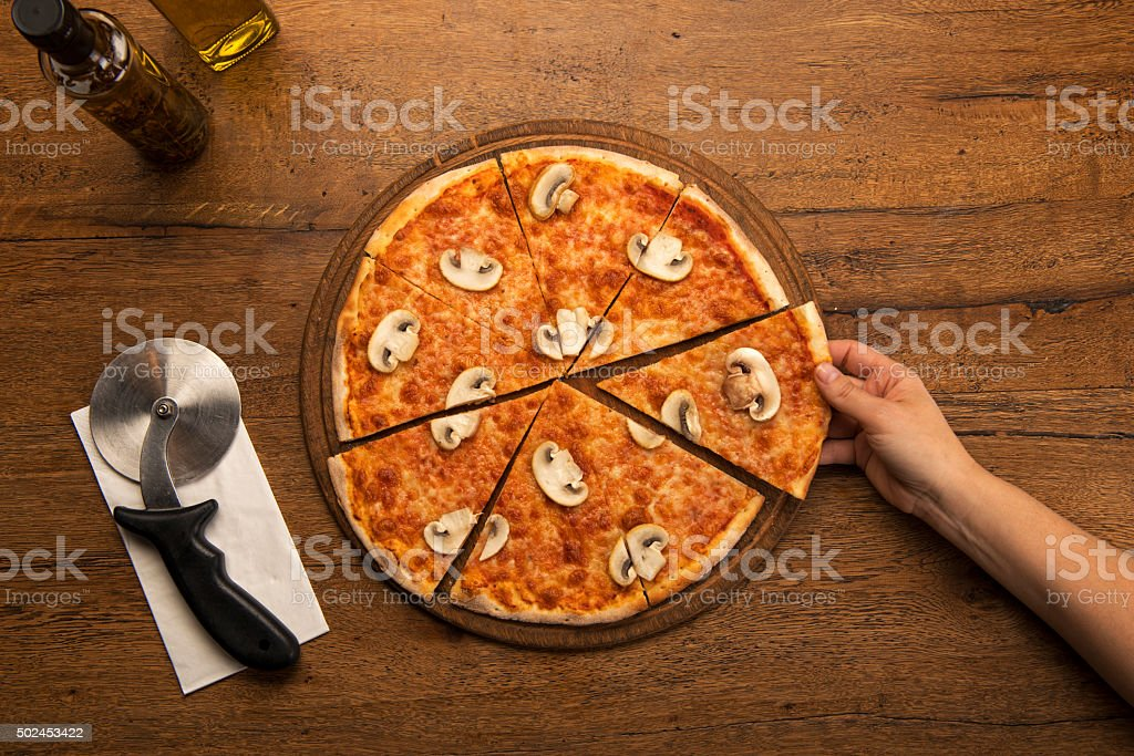 woman's hand picking a slice of mushroom pizza stock photo