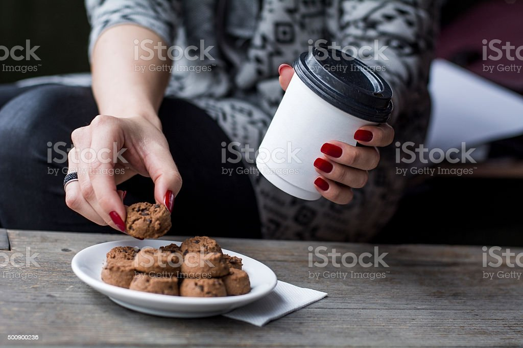 Woman's hand picking chocolate chip cookie stock photo