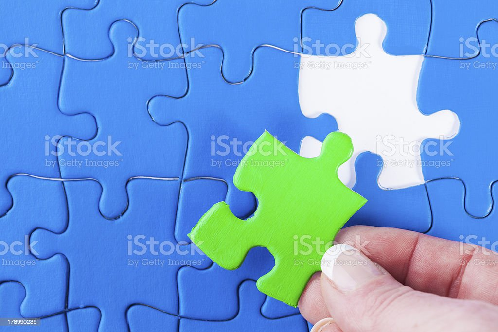 Woman's hand placing missing piece Jigsaw puzzle  problem solving stock photo