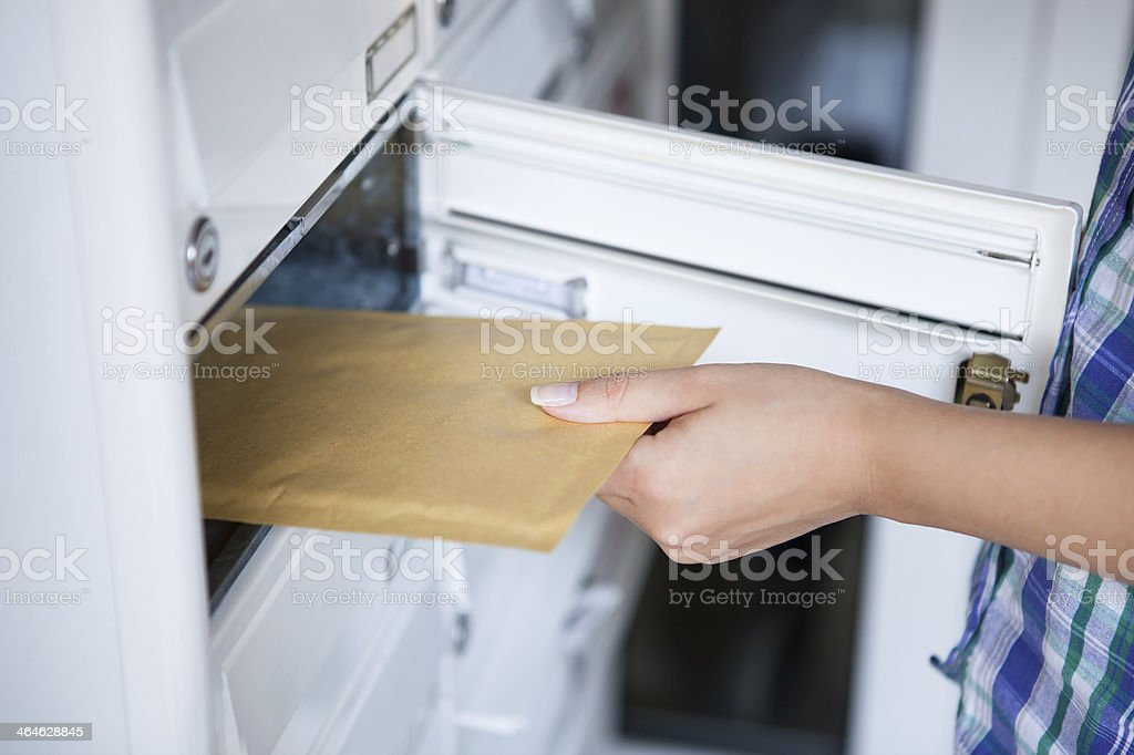 Woman's hand pulling envelop from mailbox stock photo