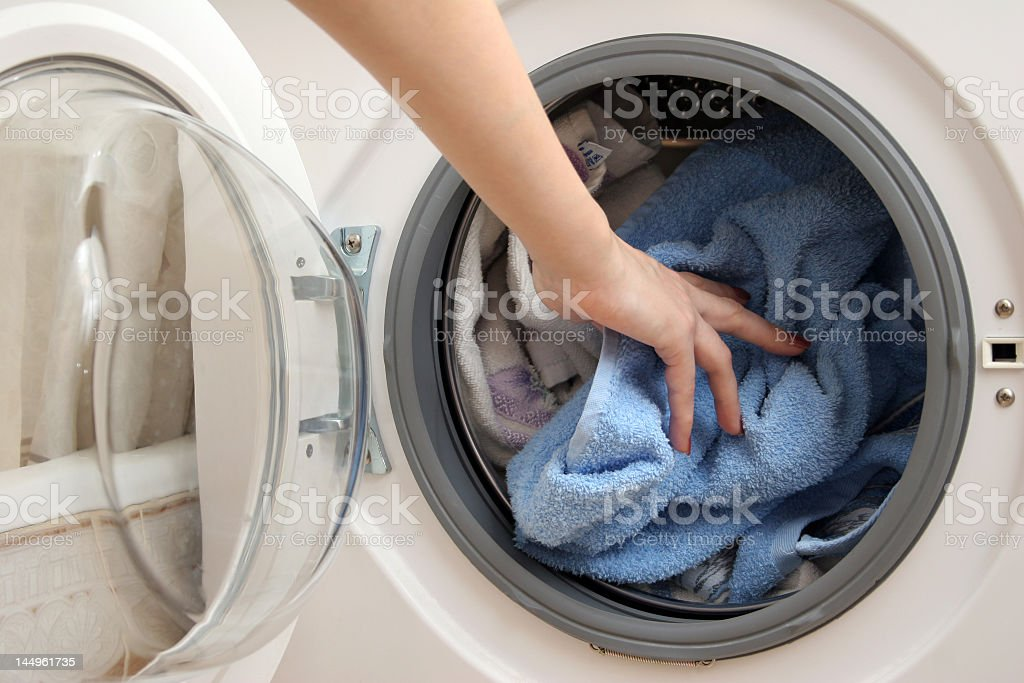 Woman's hand pushing cloths into a washing machine royalty-free stock photo