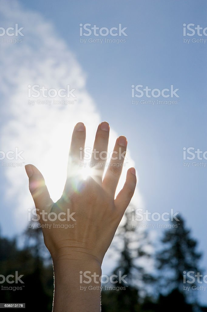 Woman's hand reaching to sky blocking sunlight stock photo