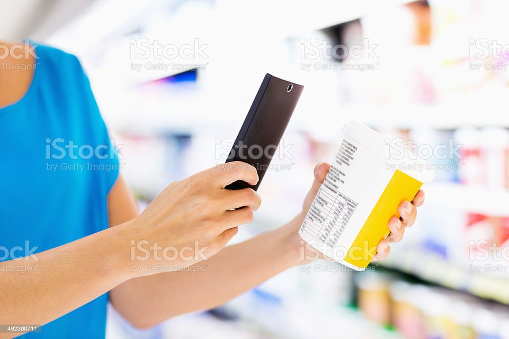 Woman's Hand Scanning Product Through Smart Phone In Store stock photo