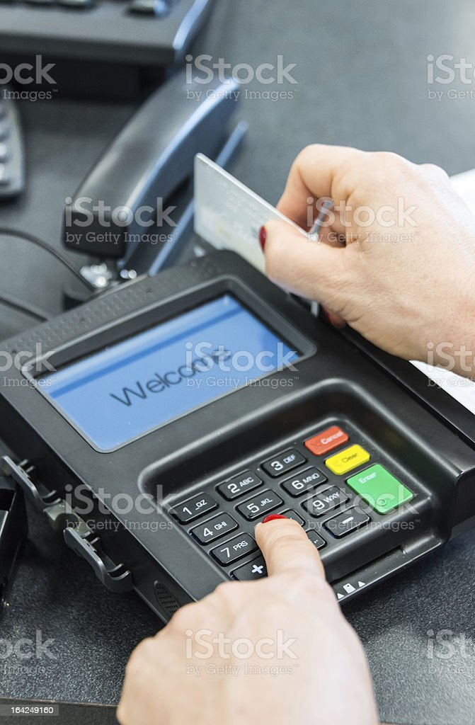 Woman's hand swipes credit card through c/c reader royalty-free stock photo