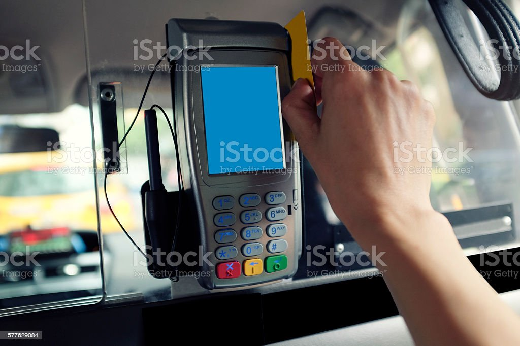 Woman's Hand Swiping Credit Card on Taxi Cab stock photo