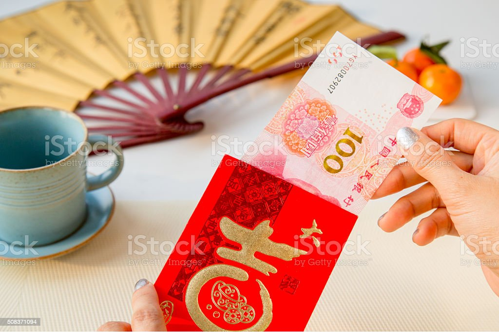 Woman's hand taking out one hundred Yuan from red envelope stock photo