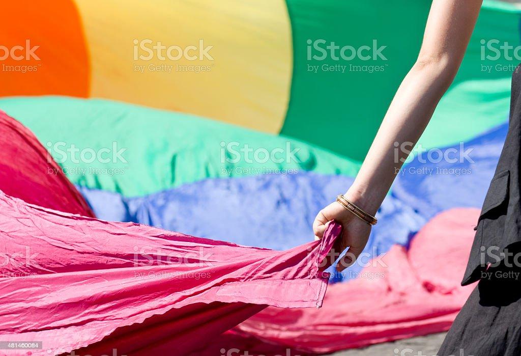Woman's hand taking rainbow peace flag stock photo