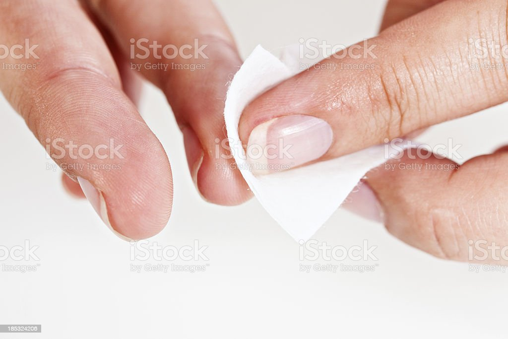 Woman's hand using sterile medical swab to cleanse finger royalty-free stock photo