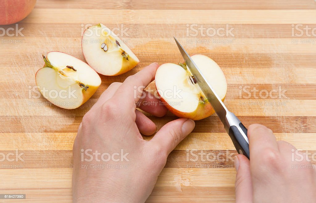 Woman's hand with a knife cuts the apples. Healthy eating. stock photo