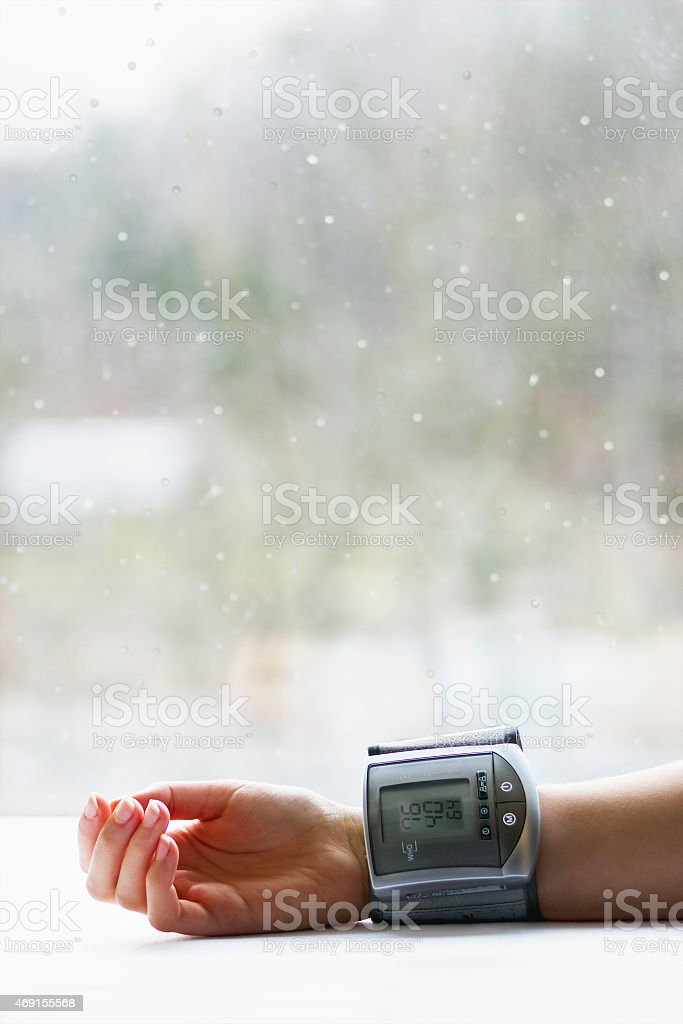 Woman's hand with blood pressure measuring device stock photo