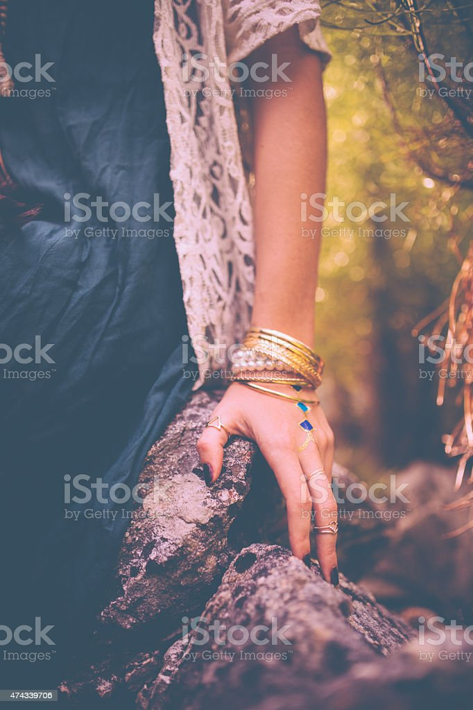 Woman's hand with boho style gold jewellery stock photo