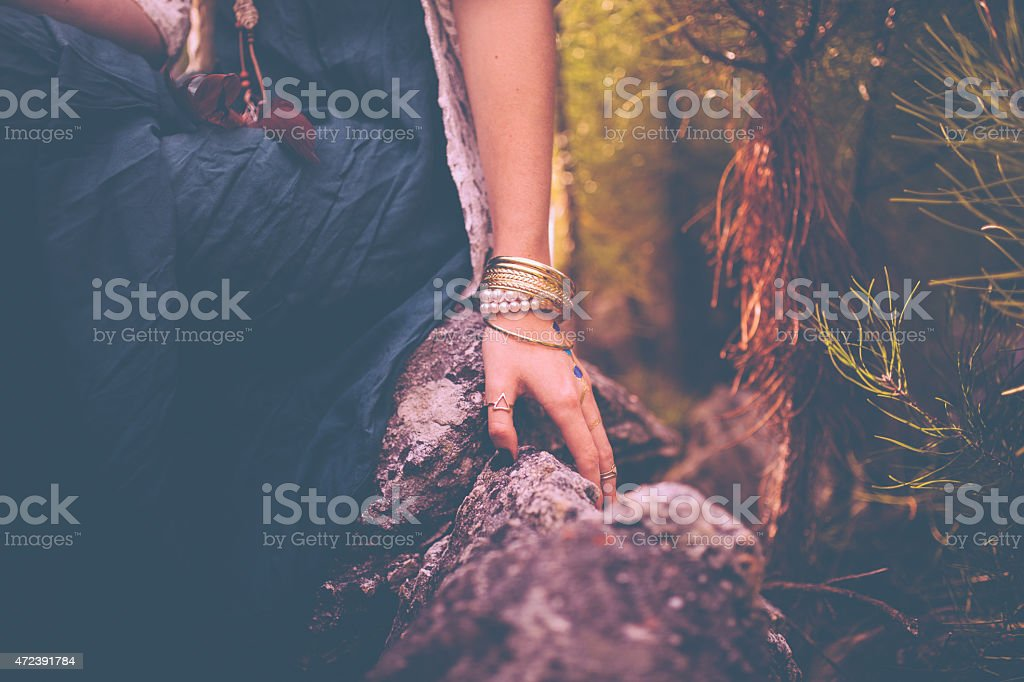 Woman's hand with boho style jewellery in nature stock photo