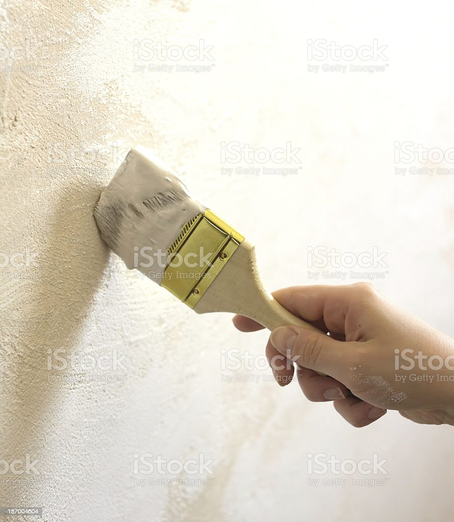 Woman's hand with brush painted wall royalty-free stock photo