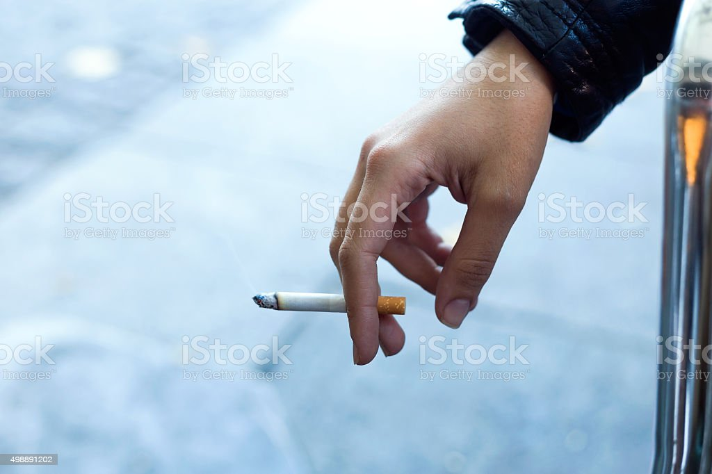 Womans hand with cigarette in the street. stock photo