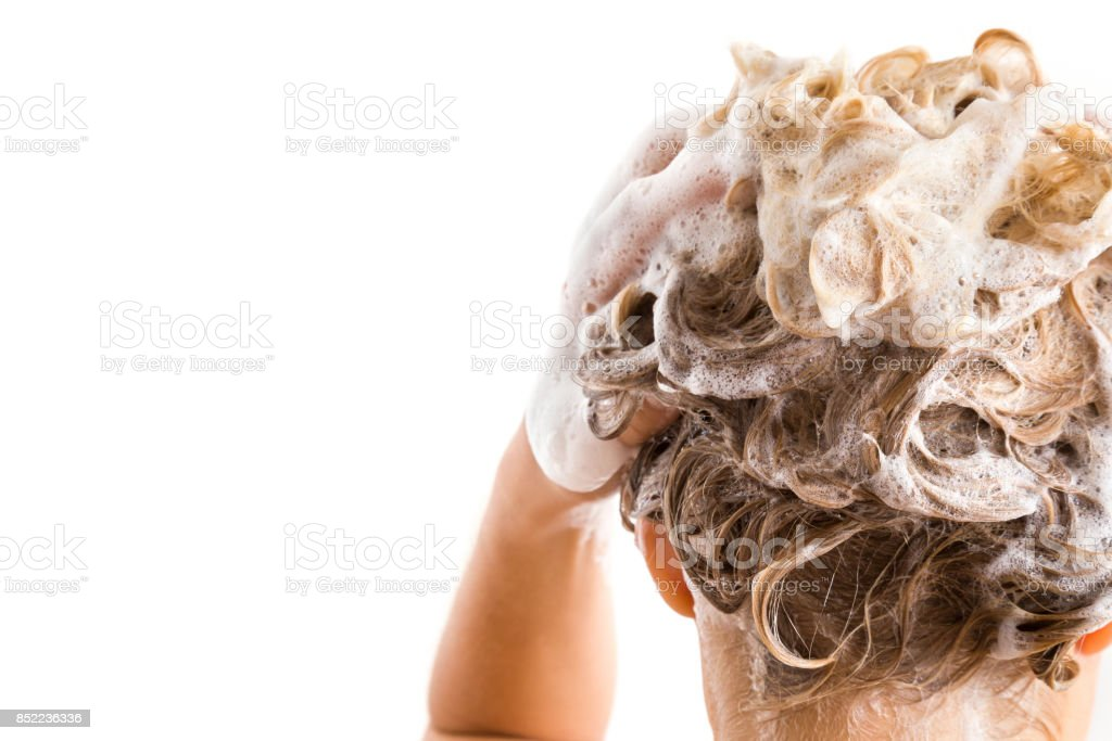 Woman's hand with shampoo washing hair isolated on the white background. Cares about a healthy and clean hair. Beauty salon. Empty place for a text. stock photo