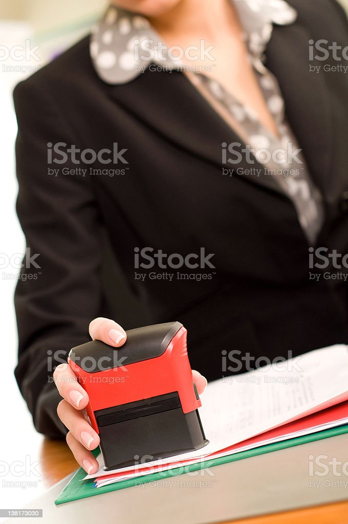 Woman's hand with stamping documents stock photo