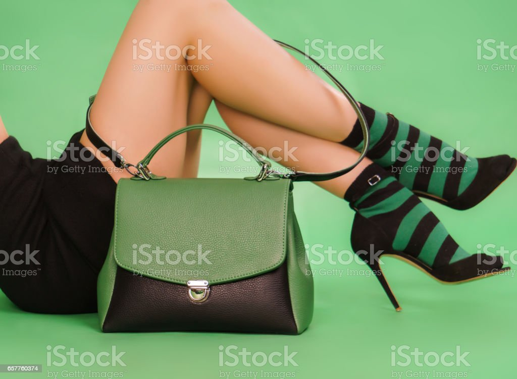 Woman's handbag and legs in a black nad green colors stock photo