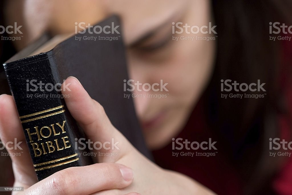 Woman's hands clasped in prayer with Holy Bible royalty-free stock photo
