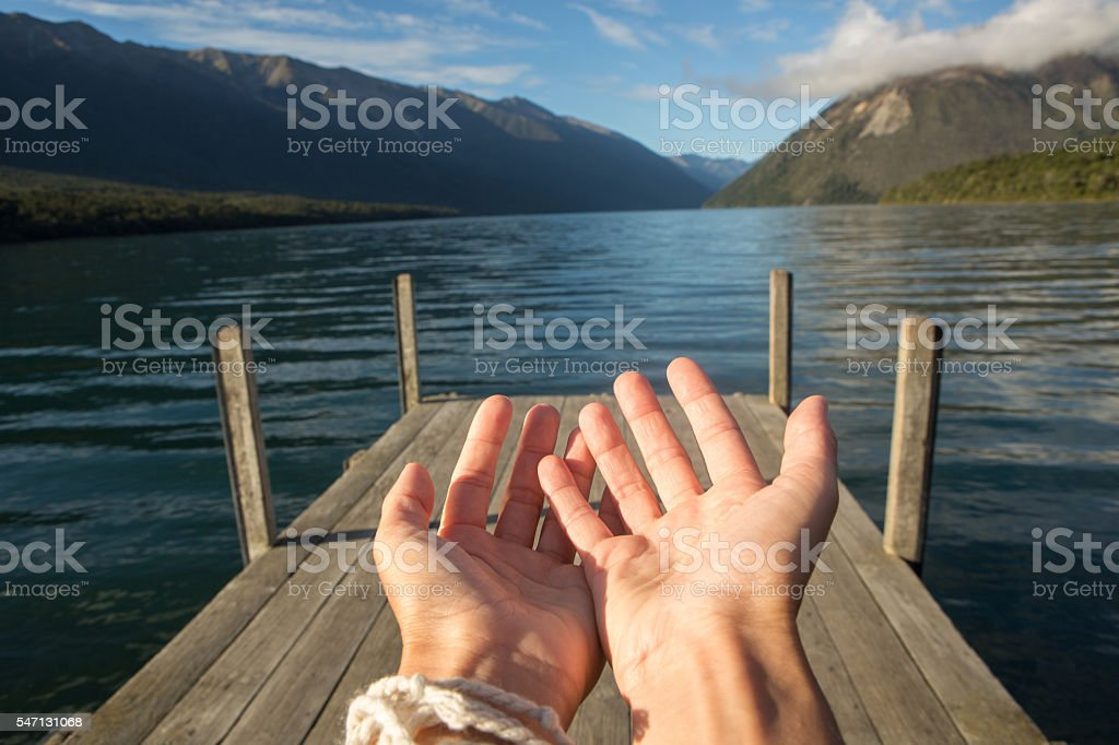 Woman's hands cupped on mountain lake landscape stock photo