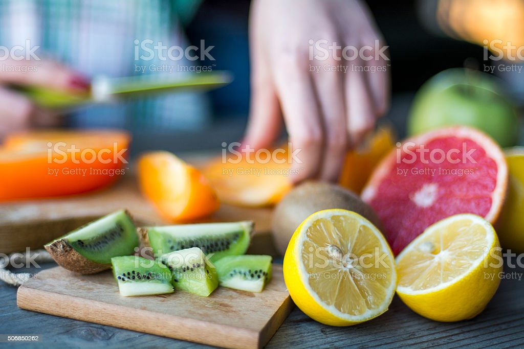 Woman's hands cuts fresh persimmons stock photo