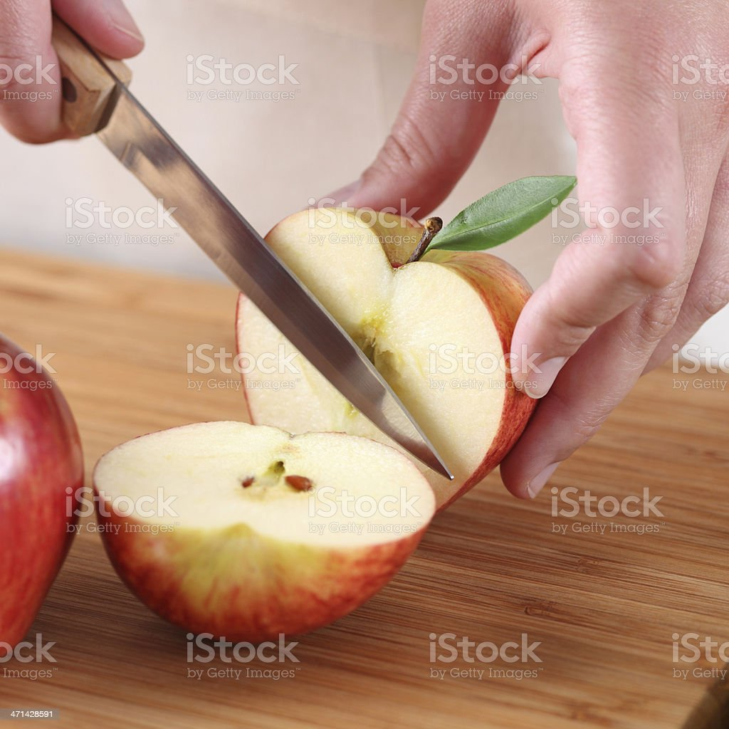 Woman's hands cutting apple stock photo