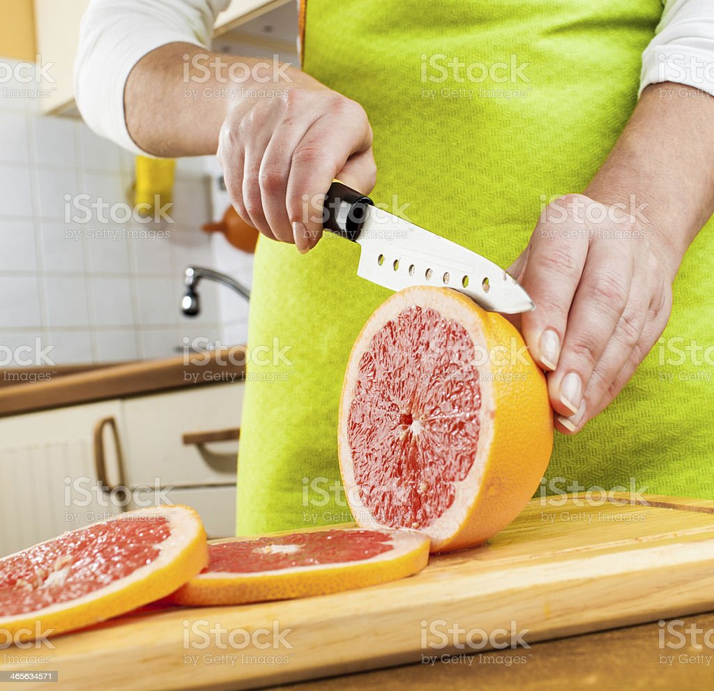 Woman's hands cutting grapefruit royalty-free stock photo