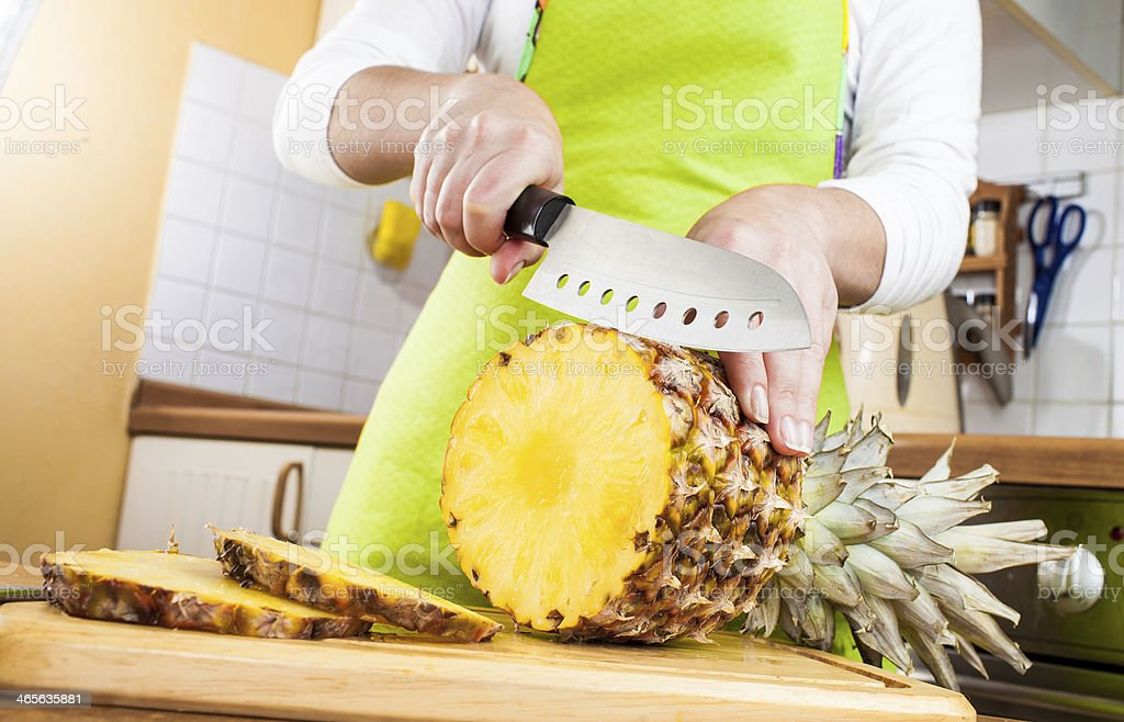 Woman's hands cutting pineapple royalty-free stock photo