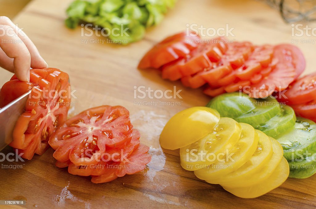 Woman's hands cutting tomato on the kitchen royalty-free stock photo