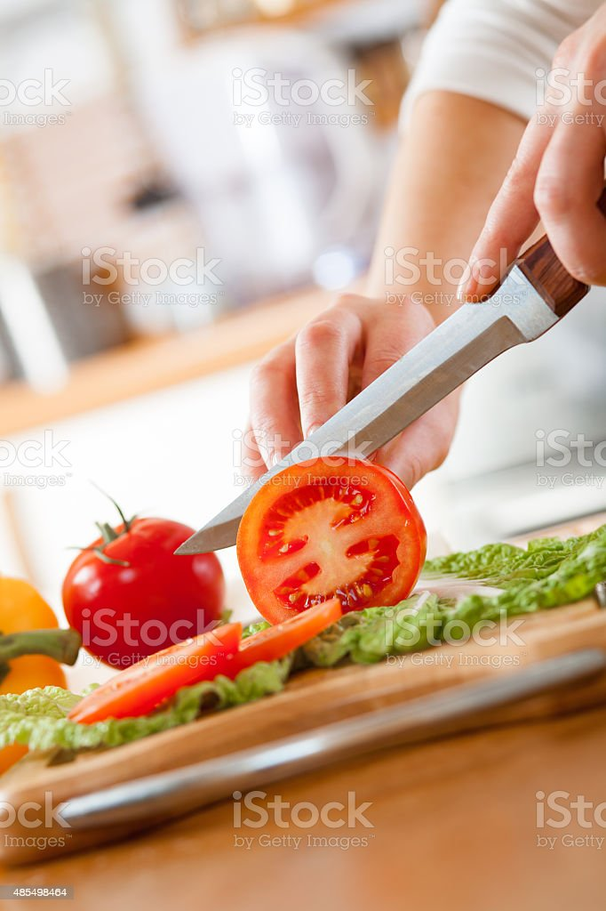 Woman's hands cutting tomato stock photo