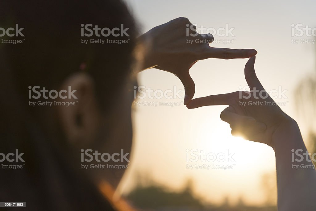 Woman's hands frame sunrise over mountain stock photo