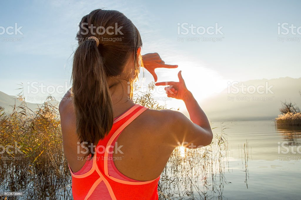 Woman's hands frame sunset over mountain lake stock photo