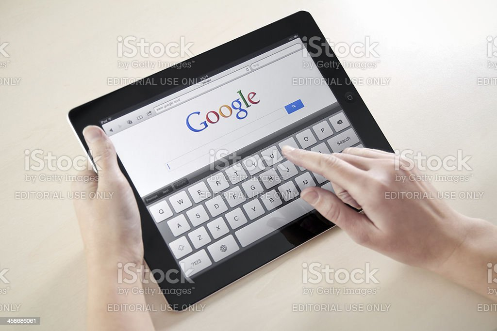 Woman's hands Googling on electronic device stock photo