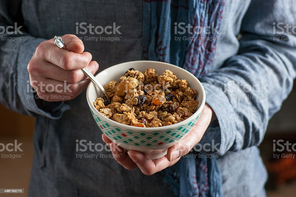 Woman's Hands Holding a Bowl Filled With Homemade Granola stock photo