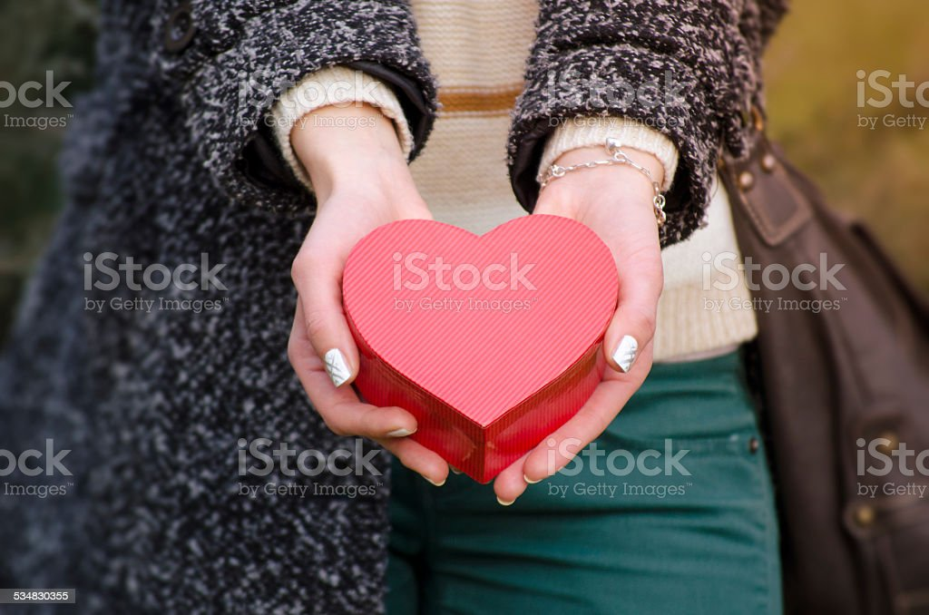 Woman's hands holding a heart shaped box royalty-free stock photo