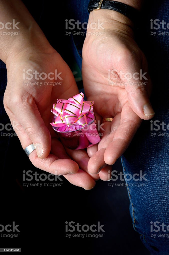 woman's hands holding a small pink heart shaped box stock photo