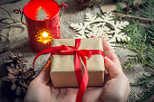 Woman's hands holding christmas decorated gift box