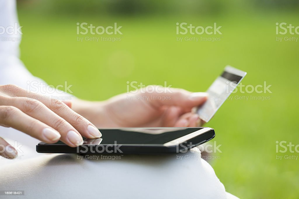 Woman's hands holding credit card and using cell phone stock photo