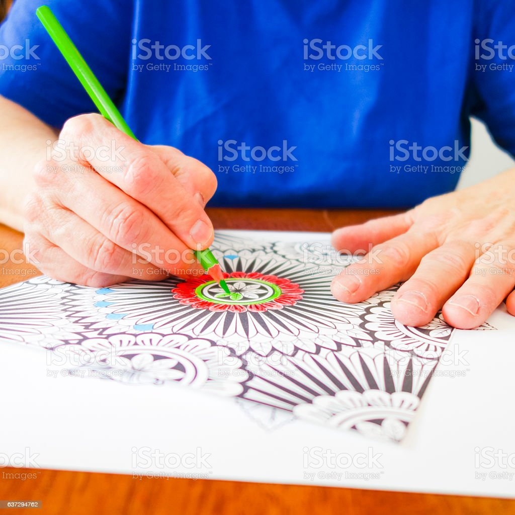 Woman's Hands Holding Green Pencil Crayon Coloring a Design Page stock photo