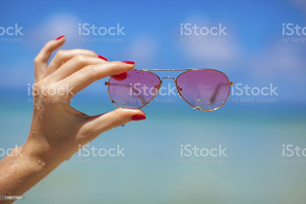Woman's hands holding pink sunglasses on tropical beach stock photo