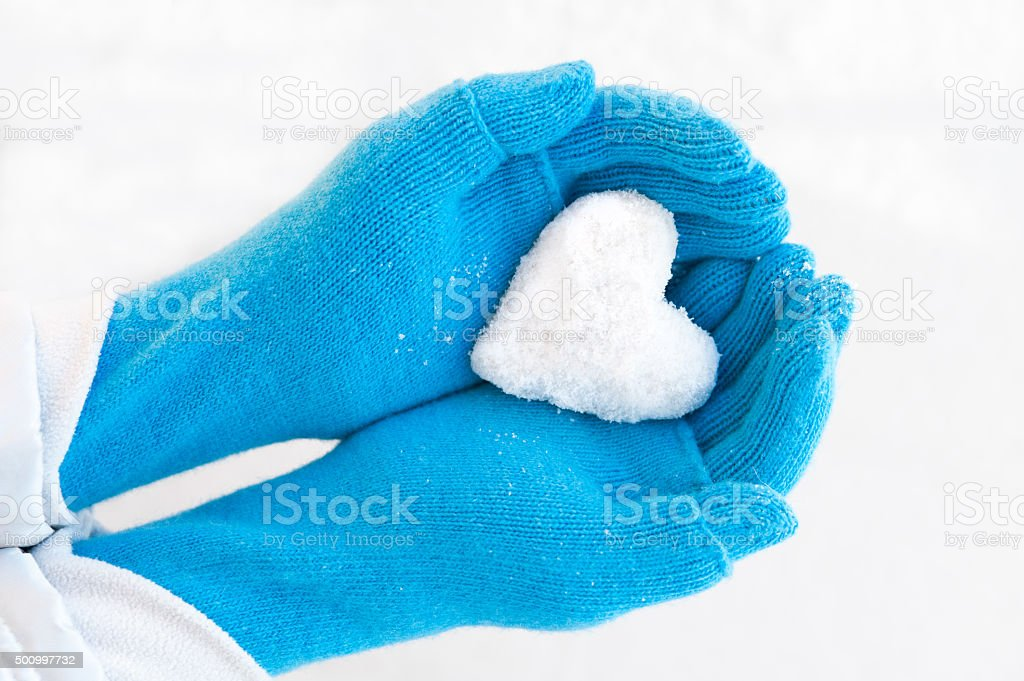 Woman's hands holding snowheart. stock photo