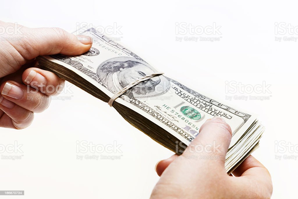 Woman's hands holding thick bundle of US dollars royalty-free stock photo