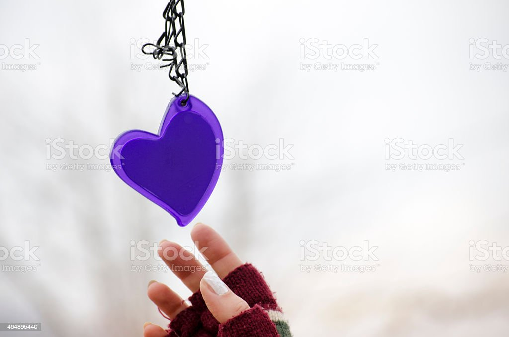 Woman's hands in mittens reaching for a heart royalty-free stock photo