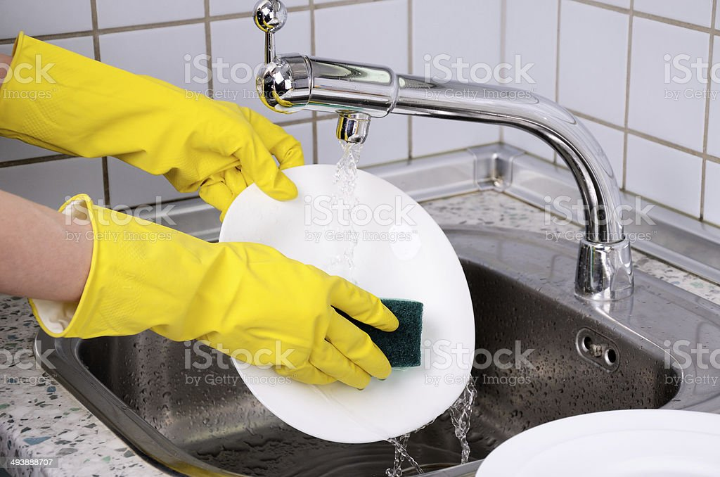 Womans hands in the gloves wash plate horizontal 0903 stock photo