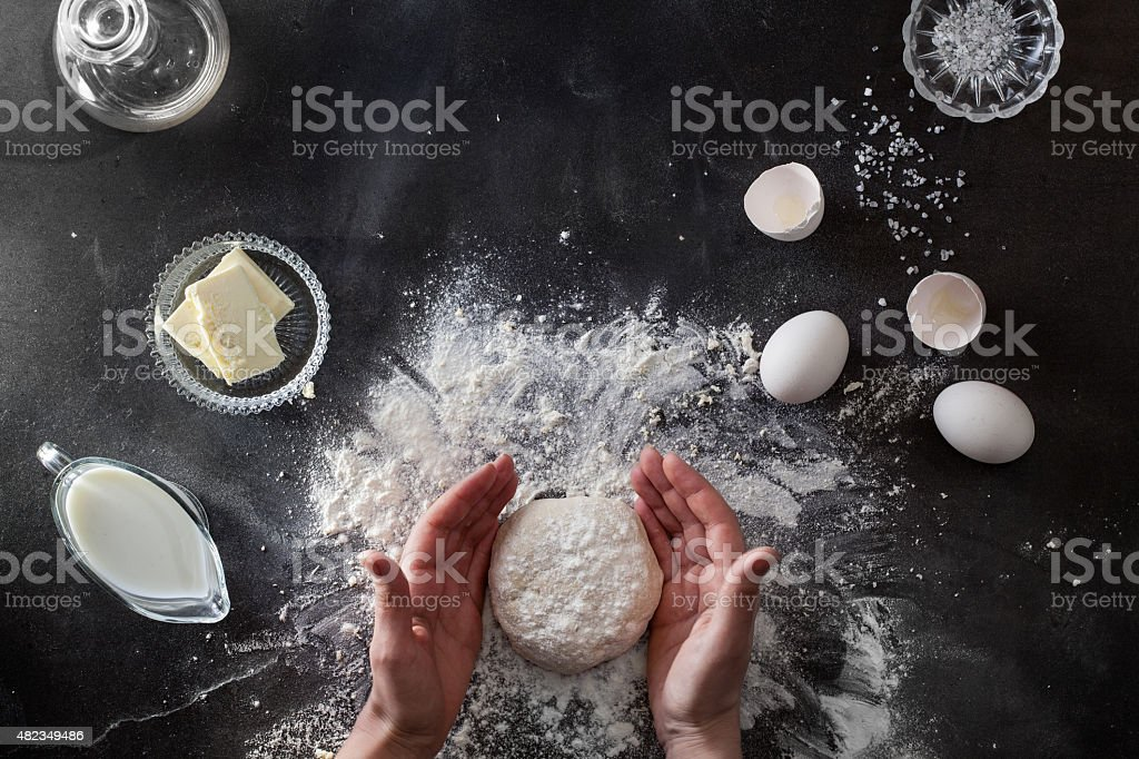 Woman's hands knead dough on table with flour stock photo