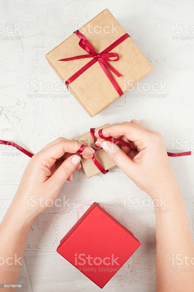 Woman's hands knotted red bow on the gift box stock photo