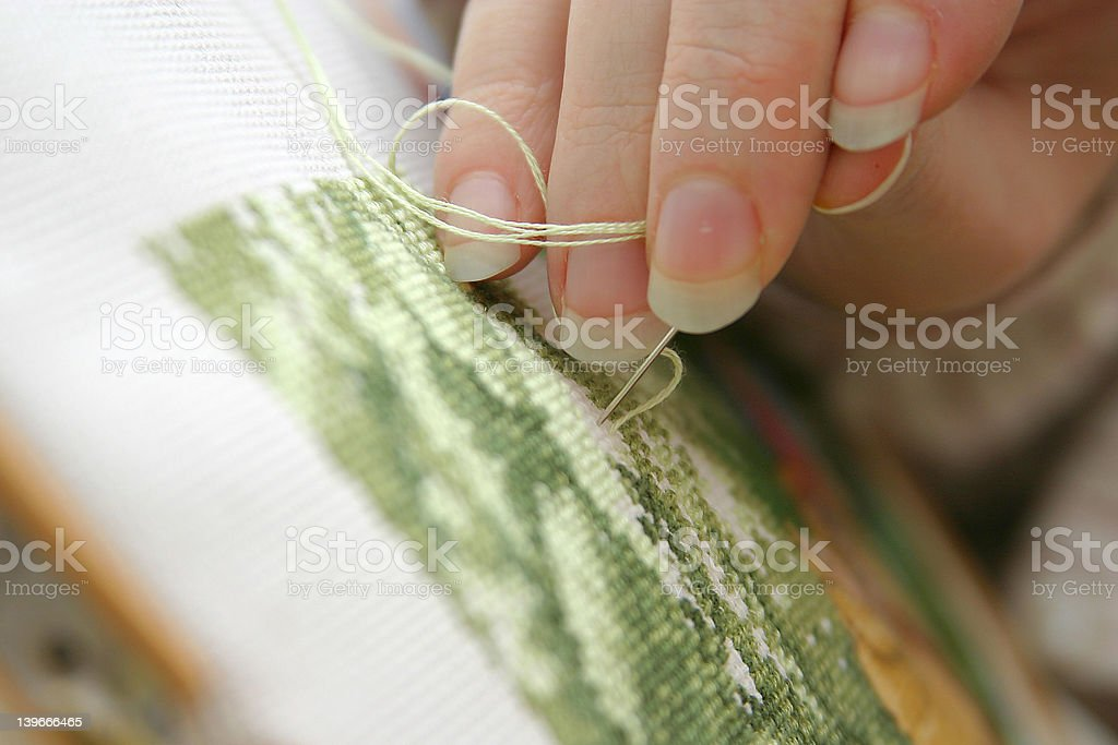 Woman's hands making a holiday cross stitch royalty-free stock photo